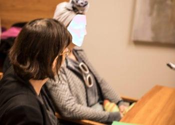 Syytetty haki oikeuden istunnossa lohtua vihreän ja oranssin kirjavista lapasistaan. Istunnon aluksi häntä tyynnytteli puolustusasianajaja Riitta Laakso. Syytetyllä oli rinnuksillaan aurinkolasit, mutta niitä hän ei kuitenkaan lopulta käyttänyt kasvojaan suojatakseen. Syytetyn kasvot on käsitelty tunnistamattomiksi.