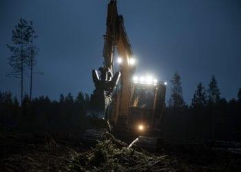 Ilta muuttuu yöksi. Sade vihmoo. Kaivinkoneen kuljettaja tekee työtään. Edessä on vielä viitisen tuntia metsänpohjan mätästystä.