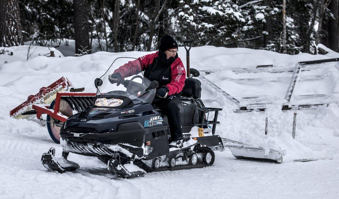 Nelitahtinen Lynxin Jeti pro -moottorikelkka perässään tällä kertaa latuhöylä ja ohjastajanaan Jukka Honko. Varikolla on monenmoista tarviketta kelkan perään kiinnitettäväksi. Puulanalla tasoittuvat kumpareet, peltilanalla lumi painetaan tiukempaan. latuhöylällä tehdään perinteisen ladut ja jyrä on käyttökelpoinen pakkaslumen käsittelyssä.