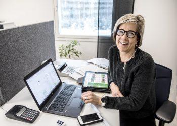 Jaana Liemola puutarhasuunnitelman äärellä uudehkoissa toimistotiloissa.
