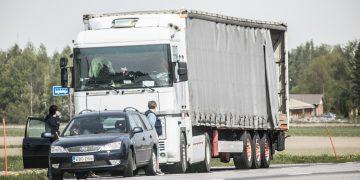 Poliisit ja kuljetusyhtiön työntekijä tarkastamassa rekkaa.