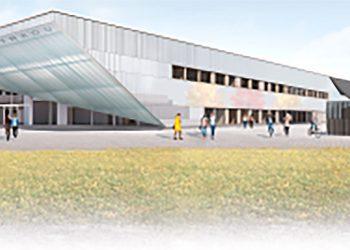 Uuden koulurakennuksen pääsisäänkäynti, jonka seinät hohtavat vaihtuvavärisen led-valaistuksen avulla.