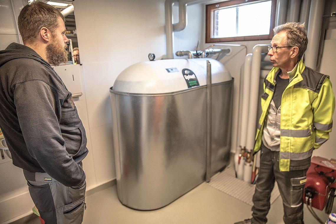 Jouni Puistola ja isännöitsijä Reijo Salonen kehuivat maalämpöä melkeinpä kilpaa. Taustalla vanhustentalojen uusi vesivaraaja, joka takaa asukkaille lämmintä vettä aina.