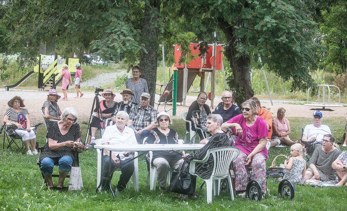 Iso osa juhlaväestä haki suojaa kuumuudelta Pihapihlajan katveesta. Pihlajan viereen on nousemassa uudeksi pihapuuksi aikanaan myös tammi. Taustalla Uotsolan toimintapuisto.